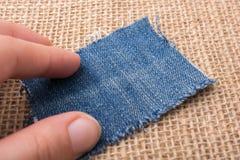 Холст джинсовой ткани в руке помещенной на linen холсте Стоковое Изображение RF