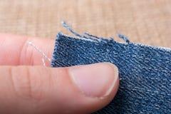 Холст джинсовой ткани в руке помещенной на linen холсте Стоковая Фотография RF