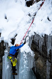 Храбрый альпинист льда взбираясь замороженный водопад в итальянских горных вершинах Стоковая Фотография RF