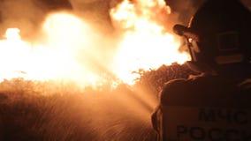 Храбрый пожарный тушит огонь на ноче сток-видео