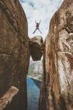 Храбрый человек скача над перемещением Kjeragbolten весьма в Норвегии стоковое изображение