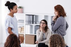 2 храбрых женщины стоя и смотря один другого во время роли оплачивая на встрече поддержки психотерапии стоковое фото rf