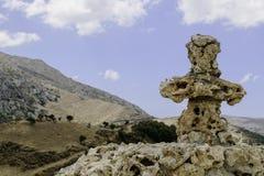 Христианский каменный крест на предпосылке облачного неба и высоких гор Стоковое фото RF