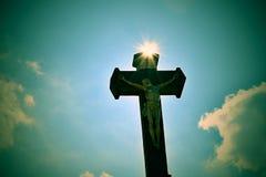 Христианский крест против голубого неба Каменный христианский крест на голубом небе с облаками и солнцем излучает Стоковая Фотография