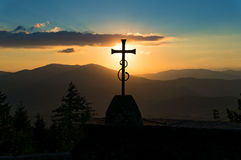 Христианский крест против захода солнца и холмов на предпосылке Стоковое фото RF