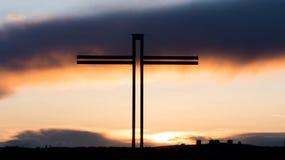 Христианский крест с красивым заходом солнца Стоковые Фото