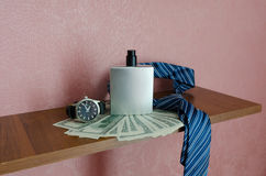 Хронометрируйте доллары галстук и бутылку дух на полке Стоковое фото RF