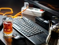 Crystal glass with black tea and computer Russian keyboard. Crystal glass of black tea. Metal teapot. Black table. Black computer keyboard. The keyboard with the royalty free stock photography