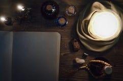 Хрустальный шар и старая волшебная книга с космосом экземпляра seance Будущая концепция чтения стоковая фотография
