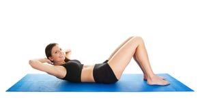 хрусты делая женщину циновки гимнастики пригодности стоковые изображения