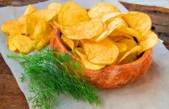 Хрустящие картофельные чипсы с укропом в деревянном шаре на салфетке белья стоковые изображения rf