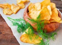 Хрустящие картофельные чипсы с укропом в деревянном шаре на салфетке белья стоковая фотография