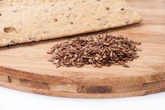 Хрустящие плиты диеты сделанные из linen и linen семян на деревянном bo Стоковые Фотографии RF