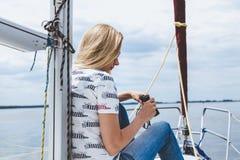 Худенькая блондинка в джинсах сидит на носе белой яхты Стоковая Фотография