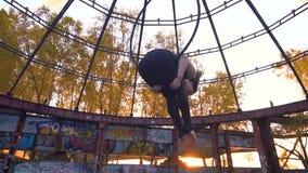 Худенькая девушка в спорт одевает падения в кольце для воздушной акробатики сток-видео