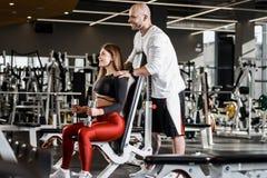 Худенькая девушка в стильных одеждах спорт сидит на гантели удерживания стенда спорт в ее руках и атлетических стойках человека стоковое фото