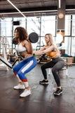 Худенькая девушка в стильных ярких одеждах спорт делая назад сидения на корточках со штангой и другая атлетическая девушка помога стоковые фото