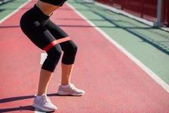Худенькая девушка фитнеса делая женщину делая сидения на корточках с резиной сопротивляется стоковое фото