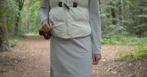 Худенькая женщина идя с камерой в коричневом случае на ее плече в лесе видеоматериал