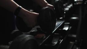 Худенькая маленькая девочка с браслетом фитнеса причаливает гантелям и принимает 2 гантели 5 kg в ее руках Для тренировки I акции видеоматериалы
