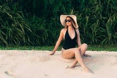 Худенькая молодая красивая девушка сидит на белом песке около тропических заводов, наслаждается релаксацией, загорает, одета в a Стоковые Фотографии RF