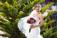Худенькая невеста в плотном платье свадьбы стоит в саде на предпосылке деревьев Порыв ветра дует она стоковое фото rf