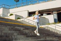 Худенькая старшая женщина бежать вниз с лестниц Стоковые Фото