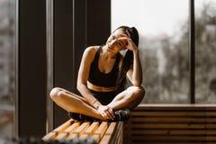 Худенькая темн-с волосами девушка одетая в черных спорт верхних и шортах сидит в представлении лотоса на деревянном силле окна в стоковое изображение