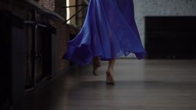 Худенькие ноги девушки с голубой юбкой делают движения танца в замедленном движении сток-видео