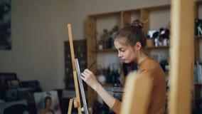 Худенький художник девушки работает в картине студии на щетке удерживания холста в грязной руке и смешивая цветах на палитре видеоматериал