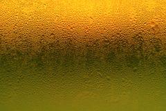 Художественная конденсация на живой бутылке стекла оранжевого и зеленого цвета стоковое изображение rf