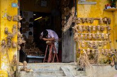 Художник высекая человеческие головы сделанные деревянных корней стоковое изображение rf