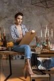 Художник девушки сидя на таблице, рисуя и смотря вперед принципиальная схема творческая Рисуя поставки, краски масла, художник Стоковое фото RF