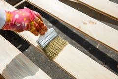 Художник держа paintbrush над деревянной поверхностью, защищая древесиной для влияний экстерьера и выдерживать Плотничество, древ стоковые фото
