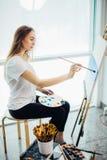 Художник, европейское море-scape чертежа девушки на холсте в ее мастерской Концепция классов изящного искусства Стоковое фото RF