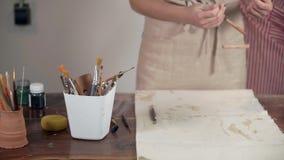 Художник женщины кладет ее аппаратуру в каботажное судно на таблицу д сток-видео
