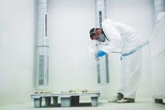 Художник используя airbrush для того чтобы покрасить нося защитную одежду Стоковая Фотография