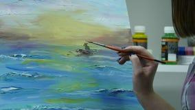 Художник красит женщину на холсте и мажет обширную щетку Холст стоит на мольберте Художник рисует на мольберте видеоматериал