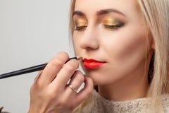 Художник макияжа в студии наводит роскошный восточный макияж к блондинке маленькой девочки, в руке которой она чистит губную пома стоковые изображения rf