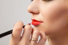 Художник макияжа в студии наводит роскошный восточный макияж к блондинке маленькой девочки, в руке которой она держит щетку для стоковое фото rf