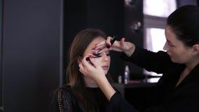 Художник макияжа делая профессионала составляет молодой женщины с длинными волосами в черном платье Тушь применяясь на длинных пл сток-видео