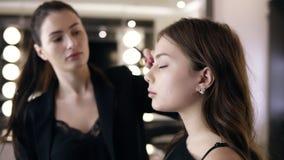 Художник макияжа используя щетку макияжа для приложения теней для век на фотомодели века Визажист делая глаза макияжа к видеоматериал