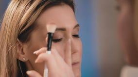 Художник макияжа нежно прикладывает темную белую тень с профессиональной белой щеткой на стороне красивого кавказца видеоматериал