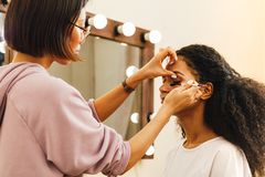 Художник макияжа прикладывая highlighter стоковая фотография