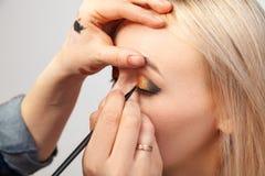 Художник макияжа с помощью щетке в одной руке рисует стрелку на глазах девушки, с другой рукой вытягивает назад стоковые фотографии rf