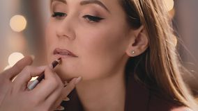 Художник макияжа формирует и рисует форму более низкой губы с карандашем на стороне красивой кавказской блондинкы сток-видео