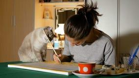Художник пробует покрасить изображение дома, но ее кот предотвращает ее от делать это Смешное любящее животное Домашний любимчик акции видеоматериалы