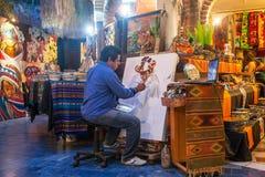 Художник работая на новой картине в искусстве и галерее сувенира внутри стоковое фото