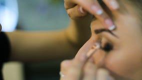 Художник состава прикладывая состав ресницы к модельному глазу ` s Закройте вверх по взгляду видеоматериал