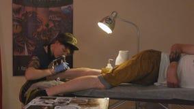 Художник татуировки девушки замедленного движения рисует на ноге Гая бесплатная иллюстрация